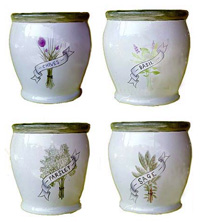 A selection of glazed ceramic pots with a herb designs forming a four piece herb set