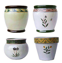 A selection of glazed ceramic outdoor pots with a raised mosaic hand painted design